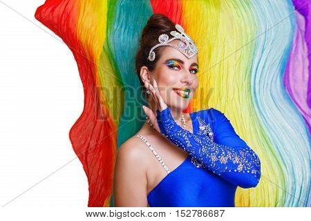 Attractive girl dancing on the background of rainbow scarf. Stage makeup and image.