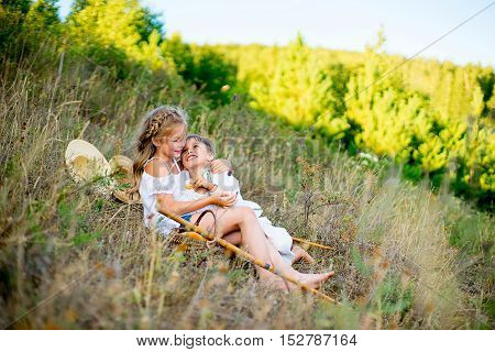 brother and sister sit on grass warm summer vacations close up