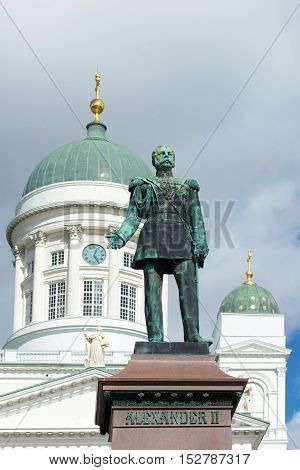 Sculpture of the Russian Emperor Alexander II (1894) on the background of the dome of Saint. Nicholas on cloudy day. Helsinki Finland