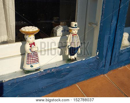 Classical vintage handmade European porcelain figurines in a window of a home