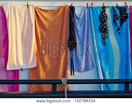 Towels and bathing swim suits drying on the clothesline on a sail boat summer background image