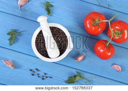 Black Pepper In Mortar And Vegetables On Blue Boards