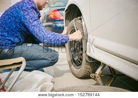 Man Changing A Wheel On The Road. On Way There Was Breakage Of Wheel, Puncture, Necessary To Lift Th