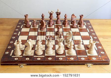 A chess pieces on the chessboard on the wooden table