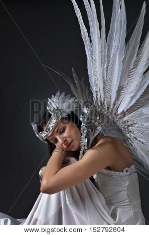 Young beautiful woman in white dress with angel wings