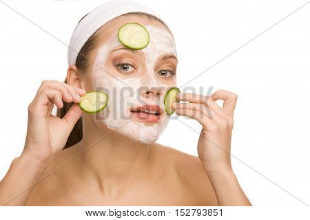 Beautiful woman is applying cucumber on her face with cosmetic mask