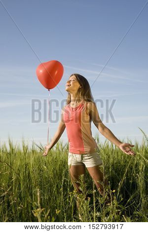 Young woman standing on the field with the red heart-shaped balloon