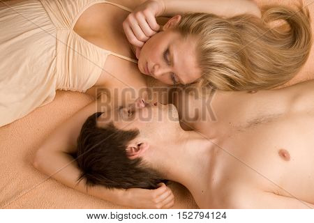 Young beautiful couple is lying on the bad face to faceclose up.Top view