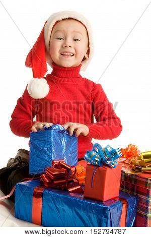 Little boy is sitting and opening a gift; isolated on white background