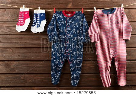 Baby boy clothes (sleepsuits and socks) hanging on the clothesline