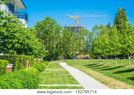 Concrete walkway in park zone along residential building. Eco friendly concept of cityscape