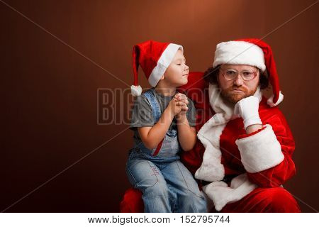 Mandressed in Santa costume looks tired and unhappy Boy is sitting on Santas knee and asking about his present. Brown backgroundcopyspace
