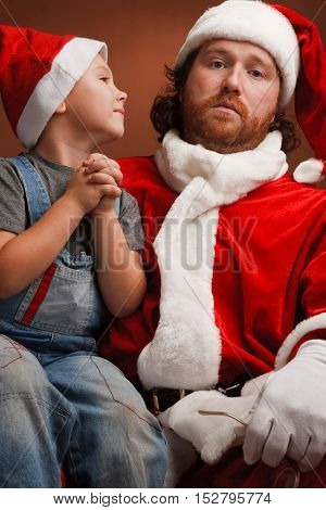 Boy is sitting on Santas knee and asking about his present. Mandressed in Santa costume looks tired and unhappy