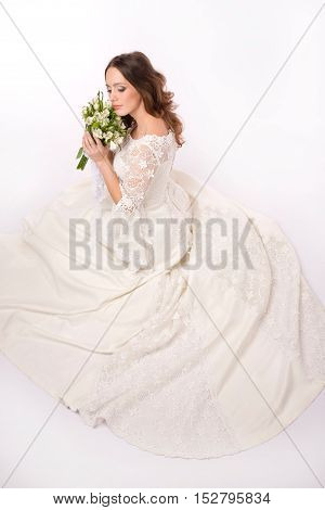 Bride dressed hippie style is sitting with flowers in her hands.High angle view