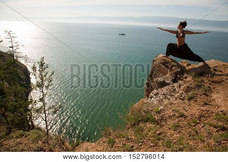 Real yoga instructor practicing on the rock near the lake.Copyspace