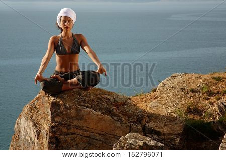 Woman real yoga instructor practicing yoga near the lake