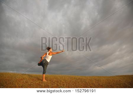 Young woman -yoga instructor is having her morning practice