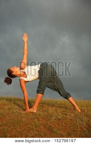 Young woman -yoga instructor is having her morning practice outdoors