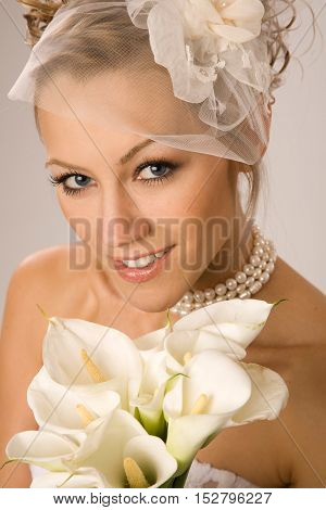 Close up of charming bride with the bouquet made of calla Lily