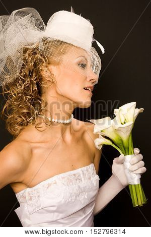 Profile of the stunning bride dressed in retro style on the black background with the bouquet made of calla Lily