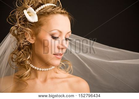 Bride with the veil and cala lily in her hairon the black background