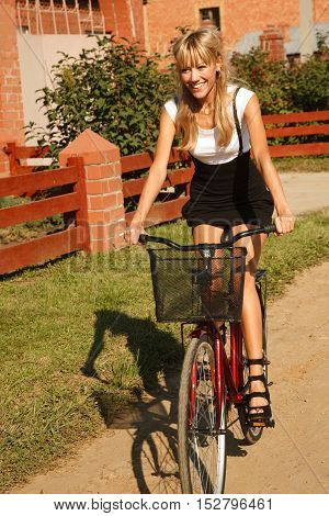 Beautiful stylish girl is riding on bicycle in the suburb