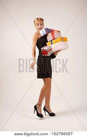Cheerful young woman is balancing with heap of gifts and loosing one