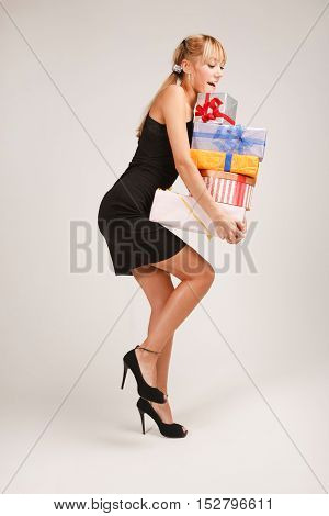 Funny young woman is balancing on one leg with heap of gifts