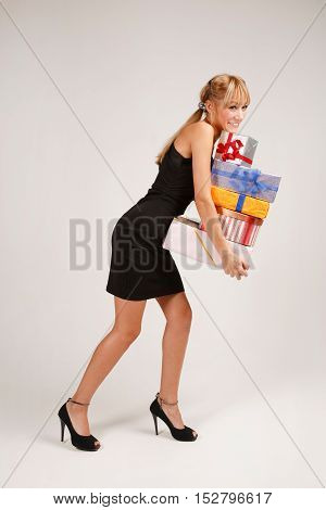 Funny young woman is sneaking with heap of gifts and loosing one