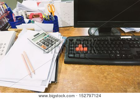 Office table with Stationery and blank desktop computer and many paperwork.