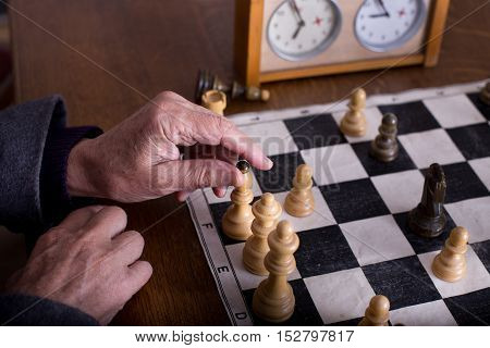 Close up of old man hands playing chess with wooden pieces