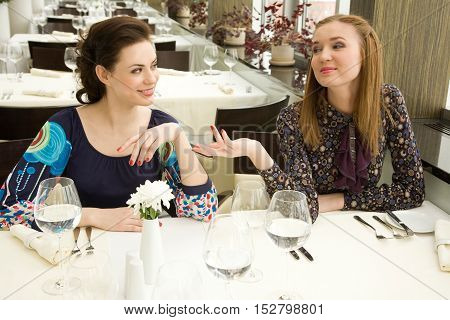 Two young woman are chatting while waiting their order in the restaurant