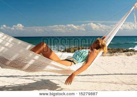Blond woman asleep in a hammock.
