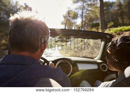 Couple driving in open top car, rear passenger point of view