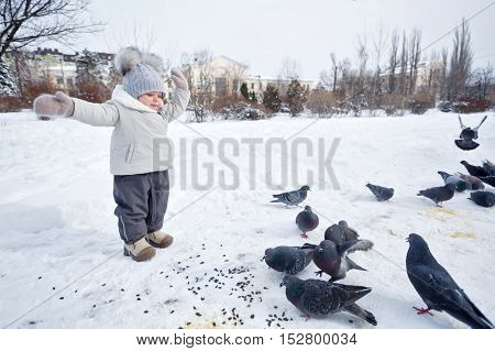 Little girl walks in a snowy winter park. She and pigeons. Happy childhood.
