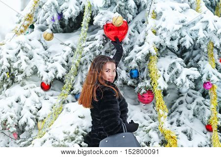 Portrait of pretty attractive girl in fur coat and gloves in the winter park. She decorates the Christmas tree balls. Winter fun. Walks in the open air.