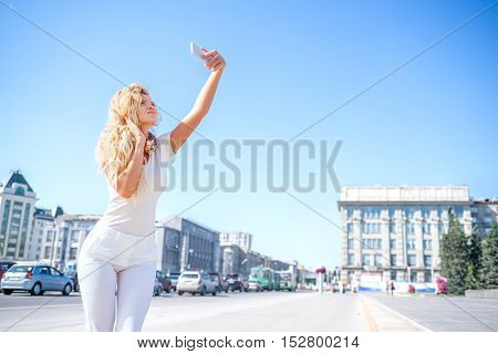 Beautiful young woman with music headphones around her neck taking picture of herself selfie against urban city background.