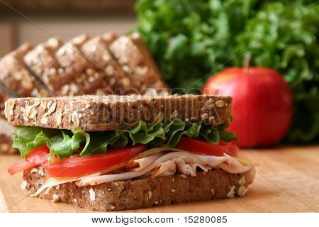 Healthy sandwich made with whole grain bread, lettuce, tomato, cheese, and roasted turkey slices.