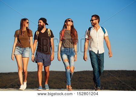 Bearded handsome men and pretty sexy cute girls or women in jeans and shorts with backpacks outdoor on sunny day walking on blue sky background