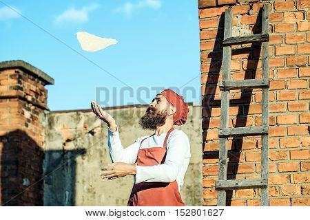 Man cook chef hipster with long beard on handsome face in red hat and white uniform throwing dough up on blue sky ladder and brick wall background outdoor