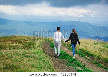 Couple Walking On Field Road