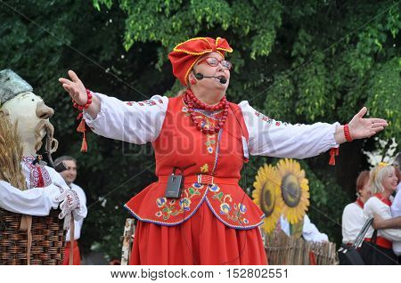 Grodno, Belarus - June 4, 2016: 11 Festival of National Cultures in Grodno, Belarus. An elderly woman in a red Ukrainian national costume standing with arms raised and sings.