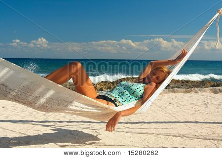 Blond woman asleep in a hammock on a tropical beach.