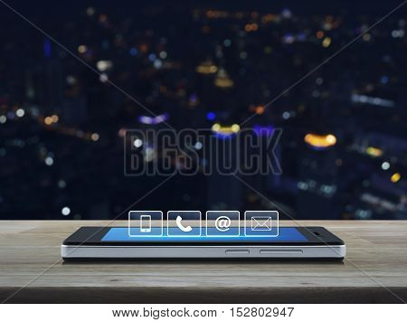 Telephone mobile phone at and email buttons on modern smart phone screen on wooden table in front of city tower background Customer support concept