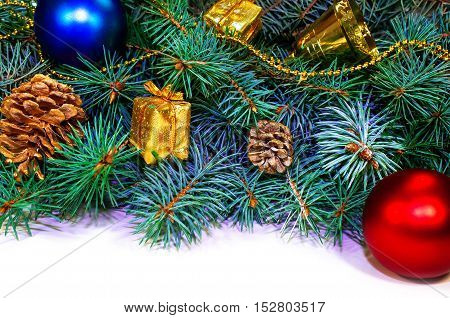 Furry Christmas tree branches with cones, gifts and toys on a white background