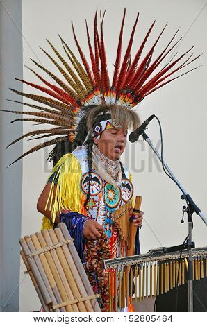 Grodno, Belarus - June 25, 2016: The city festival of street art in Grodno in June 2016. Redskin man in the national Indian suit and headdress with feathers singing in the street.