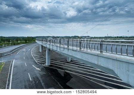 Dark clouds endless under the modern building highway.