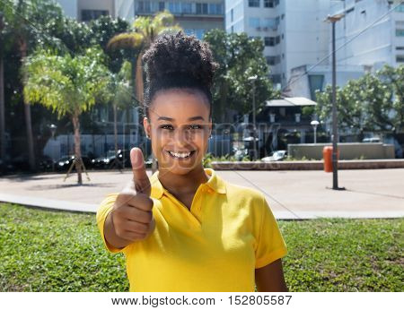 Beautiful woman with amazing hairstyle showing thumb up