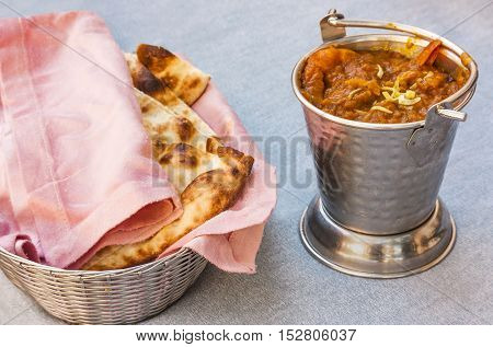 Prawn balti, an Indian dish, served in the typical dishware, with the traditional naan bread