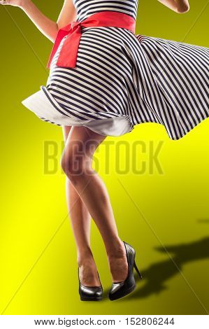 Girl Legs, A Girl In A Striped Dress. Sexually Wind Lifted The Dress.